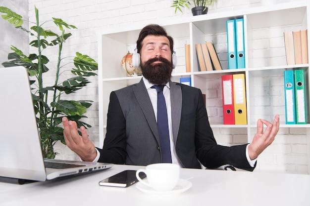 Amo meditação. empresário sente-se com gesto mudra. música para meditação. homem barbudo gosta de meditação no escritório. meditação e concentração. zen e iluminação. escute a si mesmo.