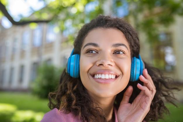 Amo música. uma jovem sonhadora sorridente com fones de ouvido ouvindo música