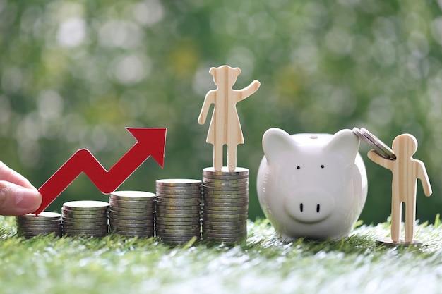 Amo o casal e a pilha de moedas de dinheiro com a mão segurando o gráfico de seta vermelha sobre fundo verde natural, investimento e conceito de negócios
