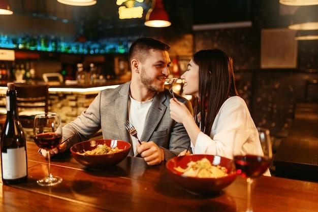 Amo o casal flertando no balcão do bar de madeira, jantar romântico com pasta e vinho tinto.