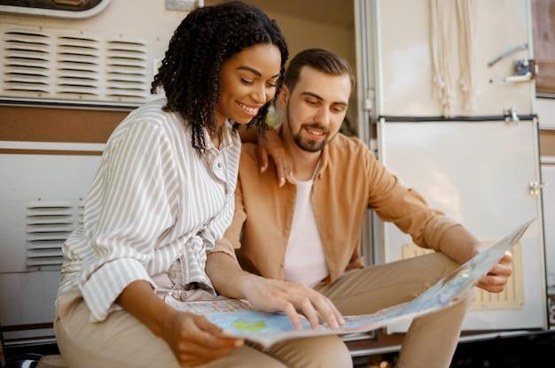 Amo o casal olhando no mapa perto de rv, acampando em um trailer. homem e mulher viajando em van, férias românticas em motorhome, lazer para campistas em carro de camping