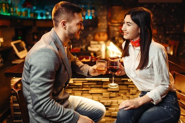 Amo o casal relaxando com álcool no balcão do bar de madeira, noite romântica.