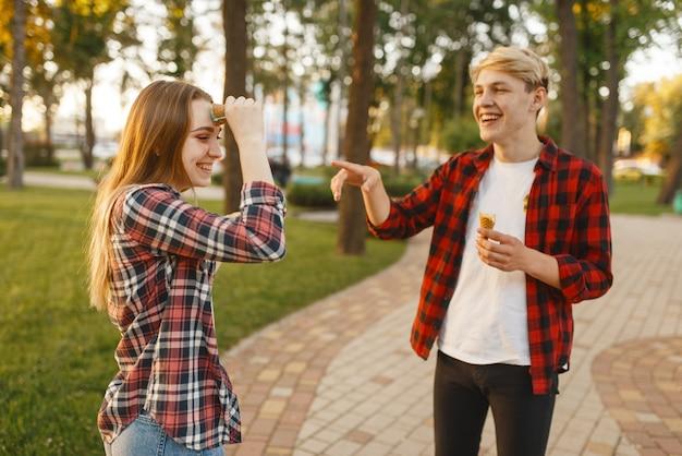 Amo o casal se divertindo com sorvete no parque de verão.