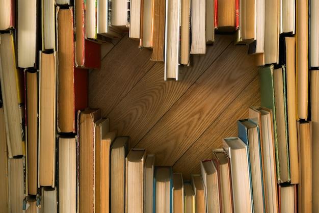 Amo o conceito de formato de coração de velhos livros vintage no chão de madeira.