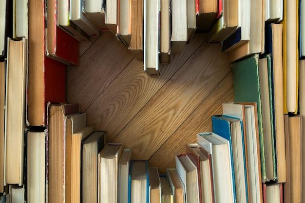 Amo o conceito de formato de coração de velhos livros vintage no fundo do assoalho de madeira. composição de estilo de tom de cor vintage de amor com formato de coração de livro aberto