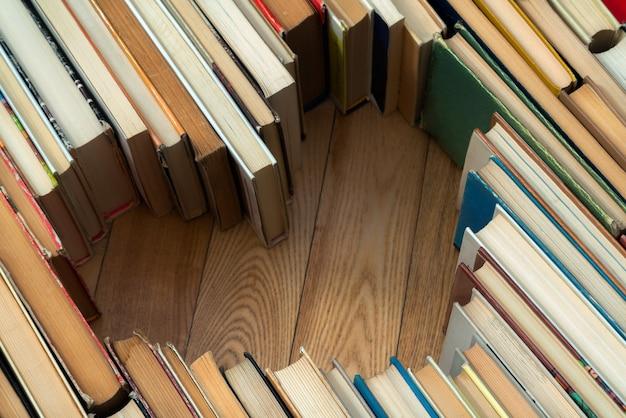 Amo o conceito de formato de coração de velhos livros vintage sobre fundo de piso de madeira.