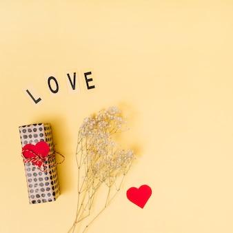 Amo o título perto da caixa de presente, enfeite de coração e plantas