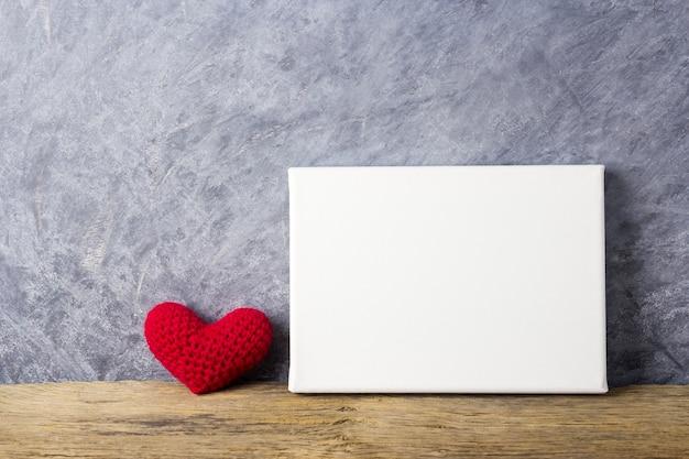 Amo os conceitos de coração vermelho e quadro de tela em branco na mesa de madeira para dia dos namorados