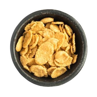 Amontoado de flocos de milho seco em uma tigela de ferro preto, vista superior close up