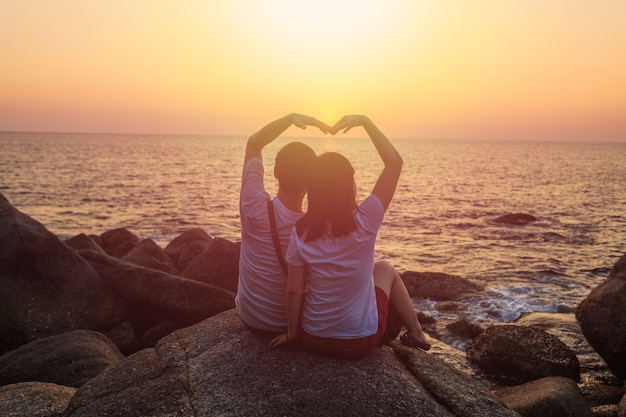 Amor asiático casal sentado na rocha no oceano e pôr do sol