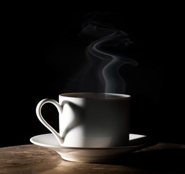 Amor café. chávena de café quente no fundo preto