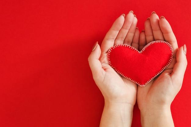 Amor, cuidado e proteção. vista superior das mãos de senhora segurando um coração de feltro feito à mão sobre o vermelho