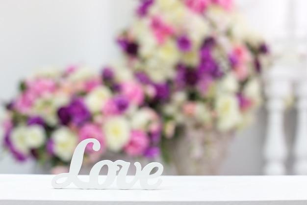 Amor de inscrição em um fundo de flores Foto Premium