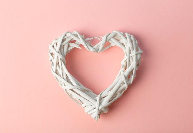 Amor (dia dos namorados) fundo ou fundo de casamento. coração branco sobre um fundo rosa pastel. conceito de amor