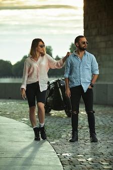 Amor e conceito romântico. casal apaixonado pelo pôr do sol no fundo, caminhando sob a ponte ao lado da motocicleta. homem com barba segura a mão da mulher, ternura.