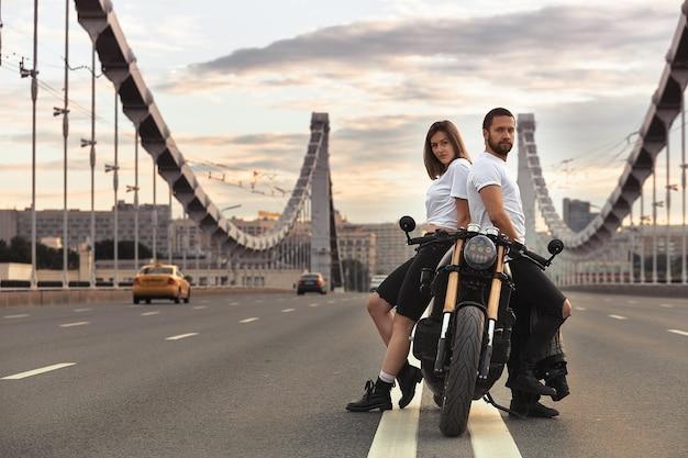 Amor e conceito romântico. lindo casal em uma motocicleta está de frente um para o outro no meio da estrada na ponte, em duplo sólido.