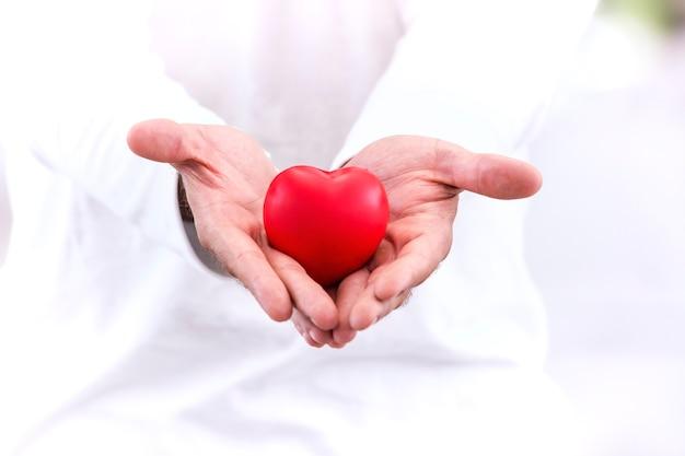 Amor e conceito saudável; coração vermelho na mão, cuide-se com amor.