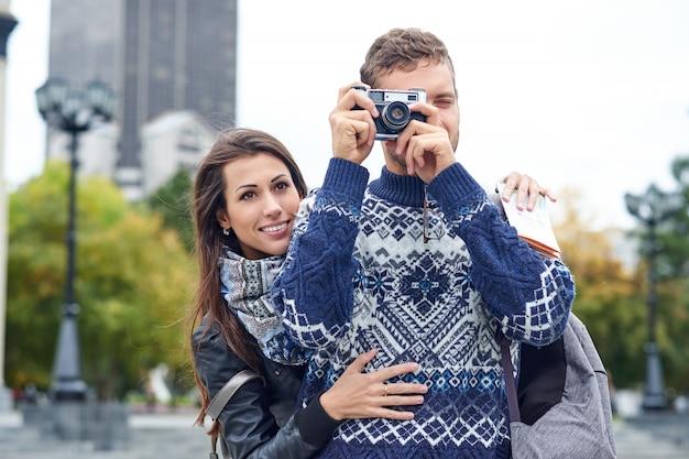 Amor feliz casal de turistas tirando foto em excursão ou passeio pela cidade. viaje junto com um mapa e uma câmera retro