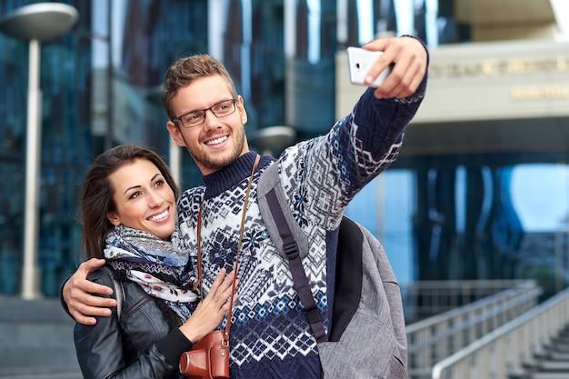 Amor feliz casal de turistas tomando selfie na cidade urbana