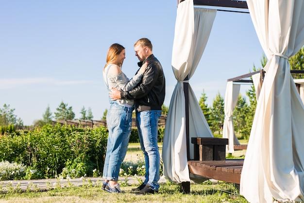 Amor, gravidez e conceito de família. homem abraçando a esposa grávida Foto Premium
