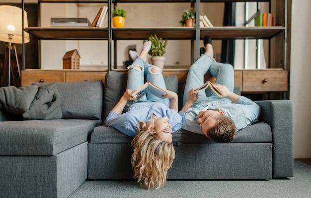 Amor jovem casal com livros deitado no sofá de cabeça para baixo.