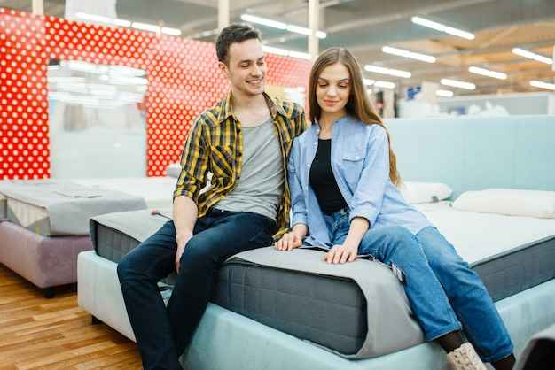 Amor jovem casal sentado na cama no showroom da loja de móveis. homem e mulher procurando amostras de quarto em uma loja, marido e mulher compram produtos para interiores modernos