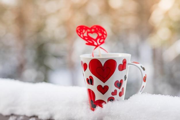 Amor na hora do café, conceito de natal, caneca e decoração de coração vermelho em uma varanda de neve.