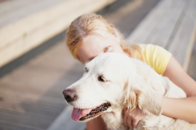 Amor para animais de estimação, uma jovem mulher loira descansando com seu cachorro na rua