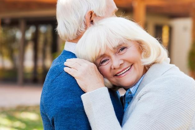 Amor para sempre. mulher idosa feliz, encostada no ombro do marido e sorrindo, enquanto os dois estão ao ar livre e na frente de sua casa