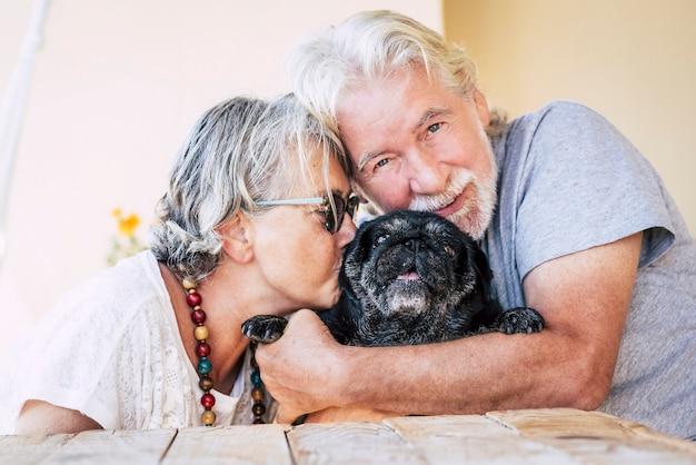 Amor pelo conceito de cachorro e animais com casal de pessoas maduras sênior e alegres e um pug preto engraçado no meio
