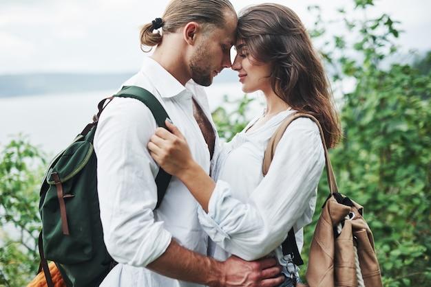 Amor profundo. jovem casal decidiu passar as férias de forma ativa perto do lago ao fundo.