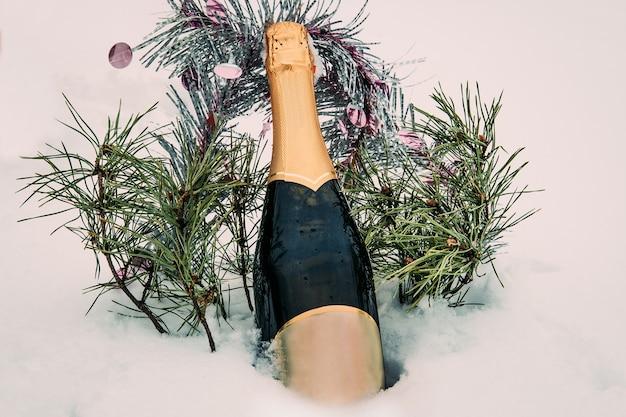 Amor, romance, férias, conceito de celebração do ano novo. garrafa de vinho branco resfriado pela neve na floresta de inverno no pôr do sol.