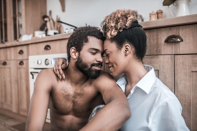 Amor. rostos jovens e felizes de um homem barbudo de pele escura e uma mulher bonita sentados com os olhos fechados e um sorriso feliz