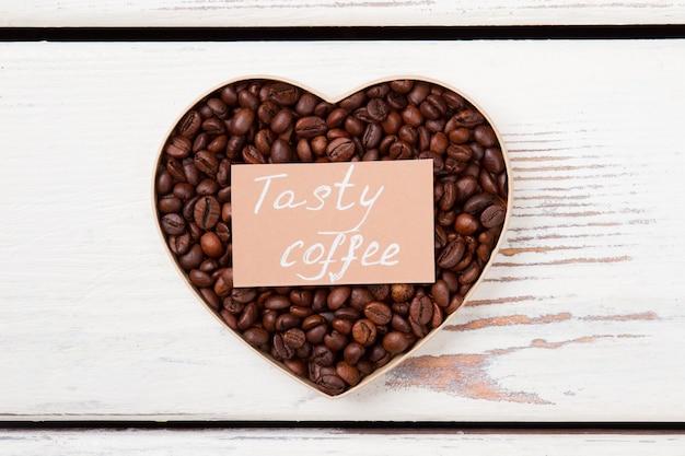 Amor saboroso do café. grãos de café marrons dispostos em forma de coração. vista superior plana.