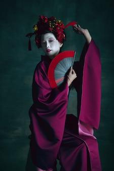 Amor trágico. jovem mulher japonesa como gueixa isolada em fundo verde escuro. estilo retro, comparação do conceito de eras. bela modelo feminina como personagem histórica brilhante, antiquada.