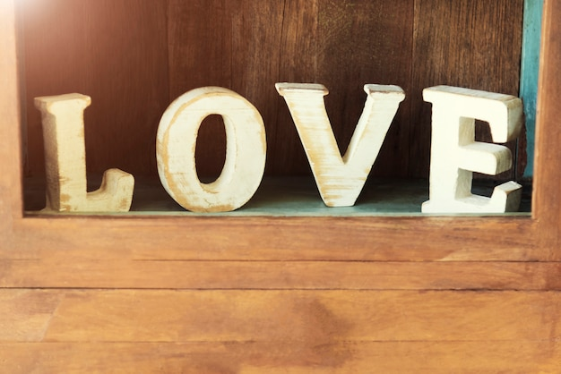 Amor, valentim e conceito do fundo do casamento caráter de madeira de love no armário de parede de madeira.