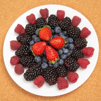 Amora, framboesa, mirtilo e morango em um prato branco. vitaminas e alimentos saudáveis
