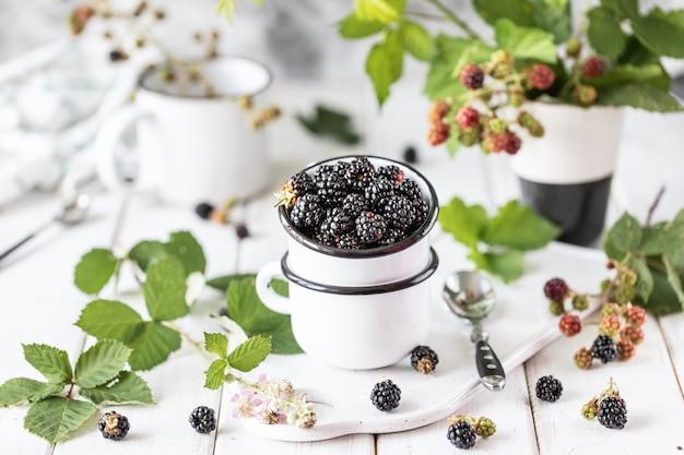 Amora-preta madura fresca em um copo cerâmico.