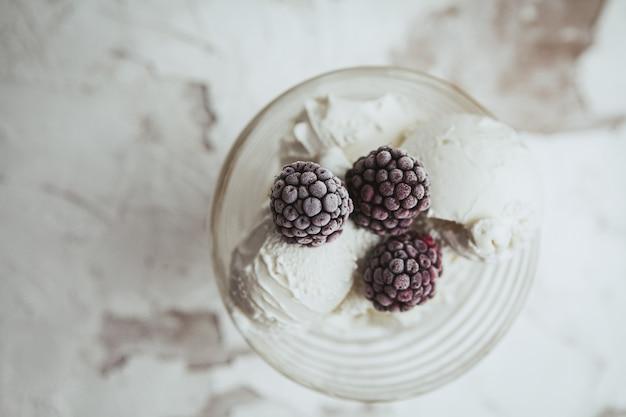 Amoras em um copo de vidro com sorvete vista superior em um branco texturizado