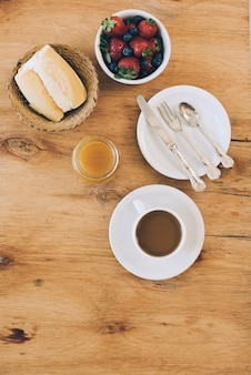 Amoras frescas; pão; geleia e xícara de café no pano de fundo texturizado de madeira