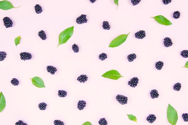 Amoras pretas deliciosas em um fundo do pêssego com as folhas verdes da manjericão.