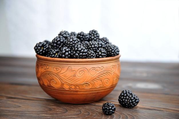 Amoras pretas em utensílios de barro em uma mesa de madeira