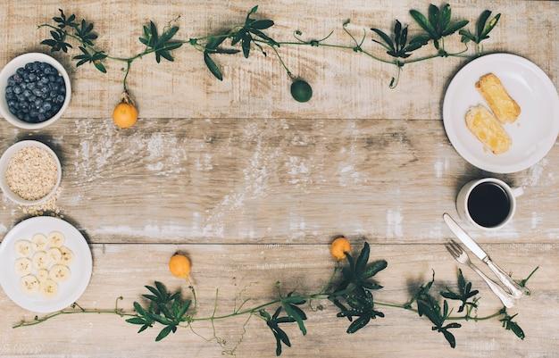 Amoras; torrada; aveia e fatias de banana com café no pano de fundo texturizado de madeira