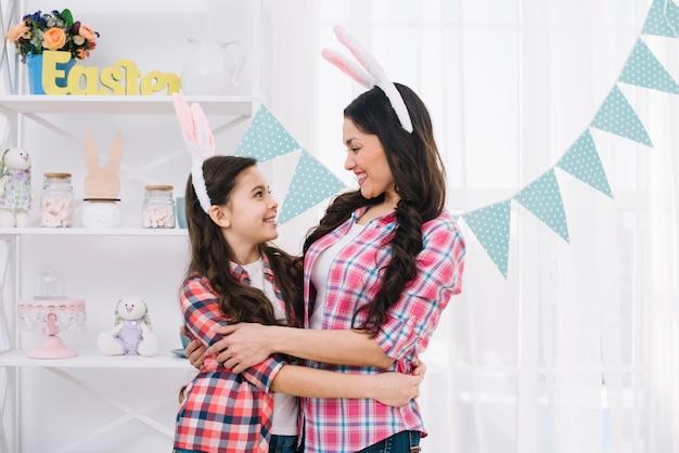 Amorosa mãe e filha, abraçando-se na celebração do dia de páscoa