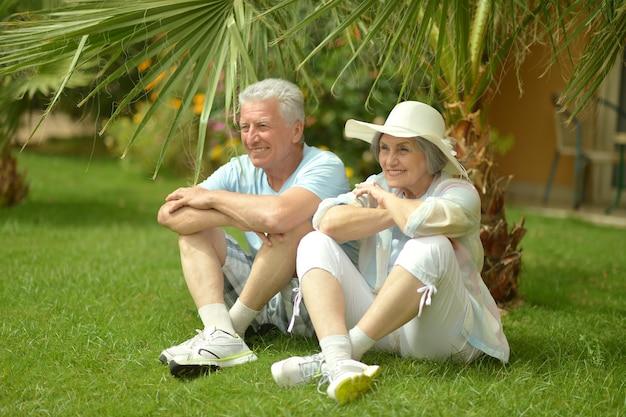 Amoroso casal de idosos sentado perto de flores e palmeiras