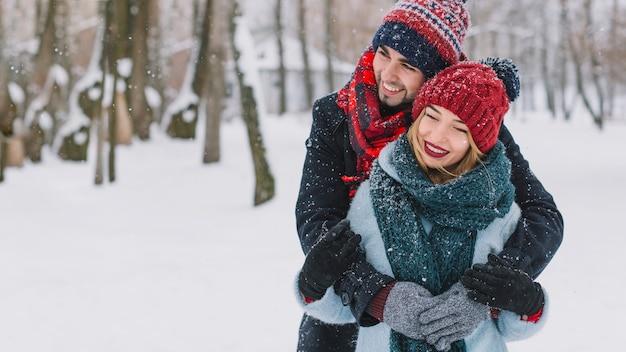 Amoroso casal feliz abraçando a queda de neve