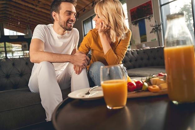 Amoroso e feliz homem casado e sua linda esposa loira e sorridente, olhando um para o outro