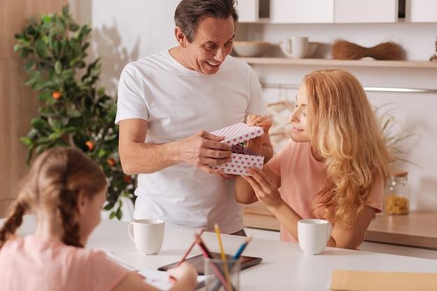 Amoroso homem maduro e alegre curtindo as férias em casa e dando um presente para a esposa enquanto a filha pinta