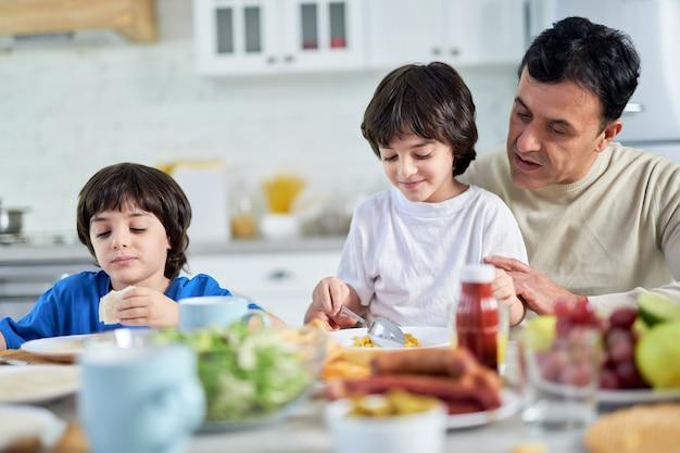 Amoroso pai hispânico de meia-idade servindo seu filho pequeno, sentado com as crianças na mesa da cozinha, enquanto tomava o café da manhã em casa. paternidade, conceito de cuidado. foco seletivo
