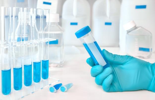 Amostra de líquido na mão feminina enluvada, amostras de líquido azul em tubos de vidro e plástico